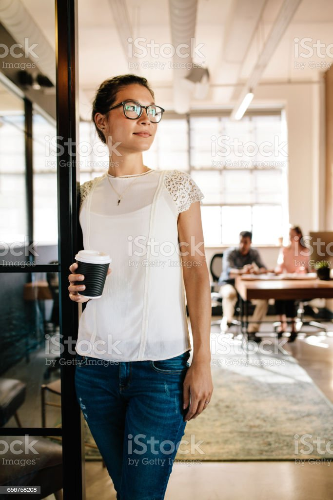 Beautiful woman in office doorway with coffee stock photo
