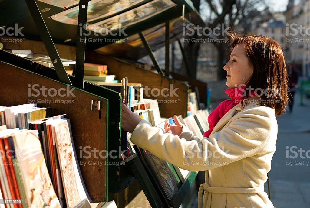 Beautiful woman in Paris selecting a book stock photo