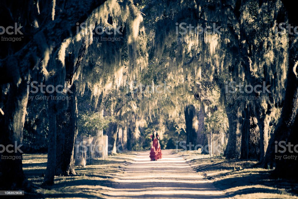 Beautiful woman in red dress walking down white sand road royalty-free stock photo