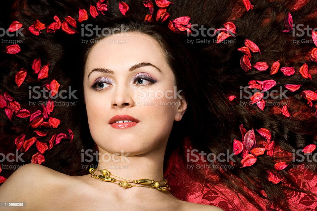 Beautiful woman in red petals royalty-free stock photo