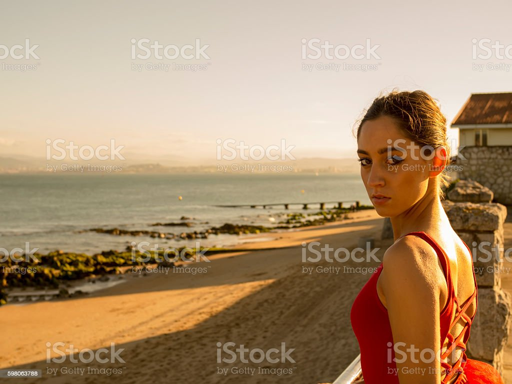 Beautiful woman in red top  against of summer coast stock photo