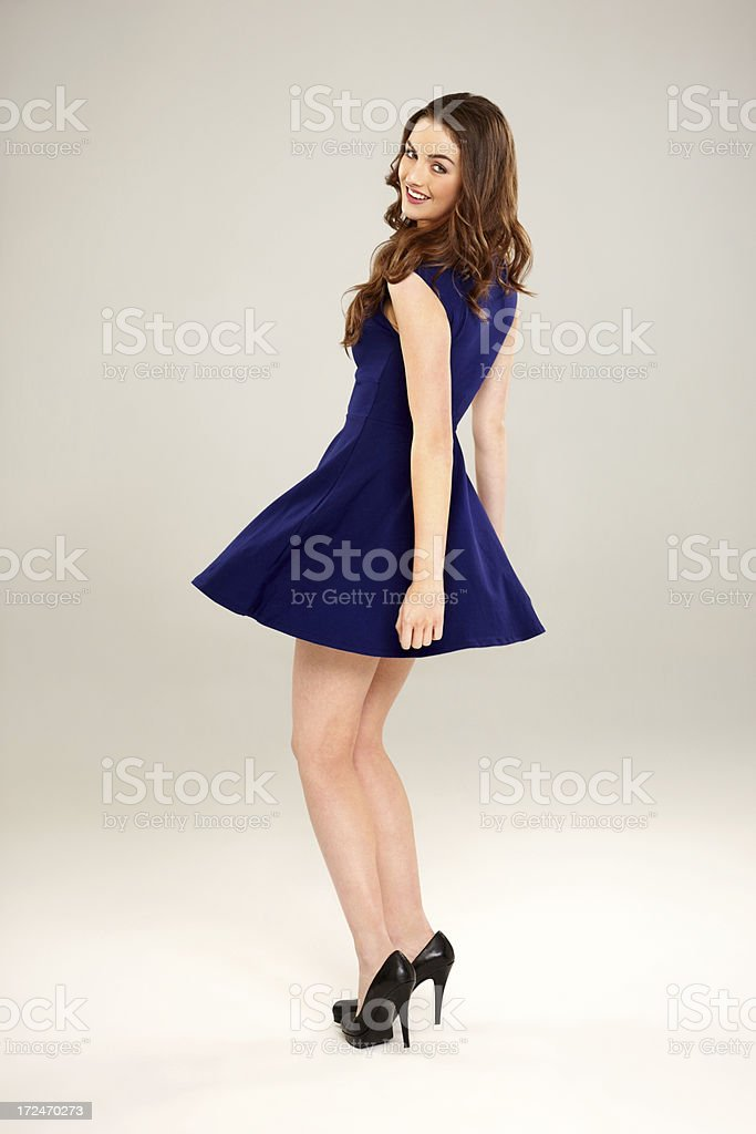 Beautiful woman in short blue dress posing over grey background stock photo