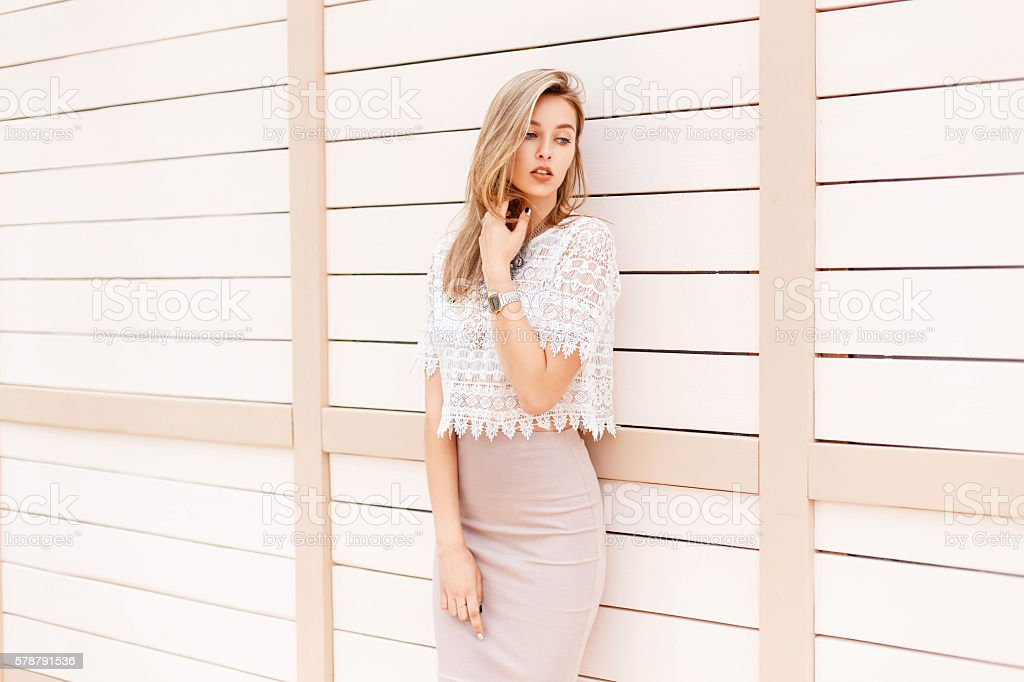 Beautiful woman in summer shirt with vintage lace near wall stock photo