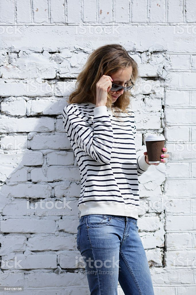 Beautiful woman in sunglasses with a disposable cofee cup stock photo