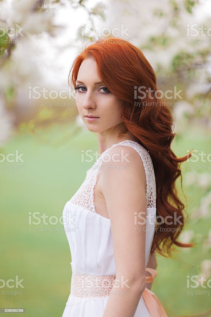 Beautiful woman in the flowering park stock photo