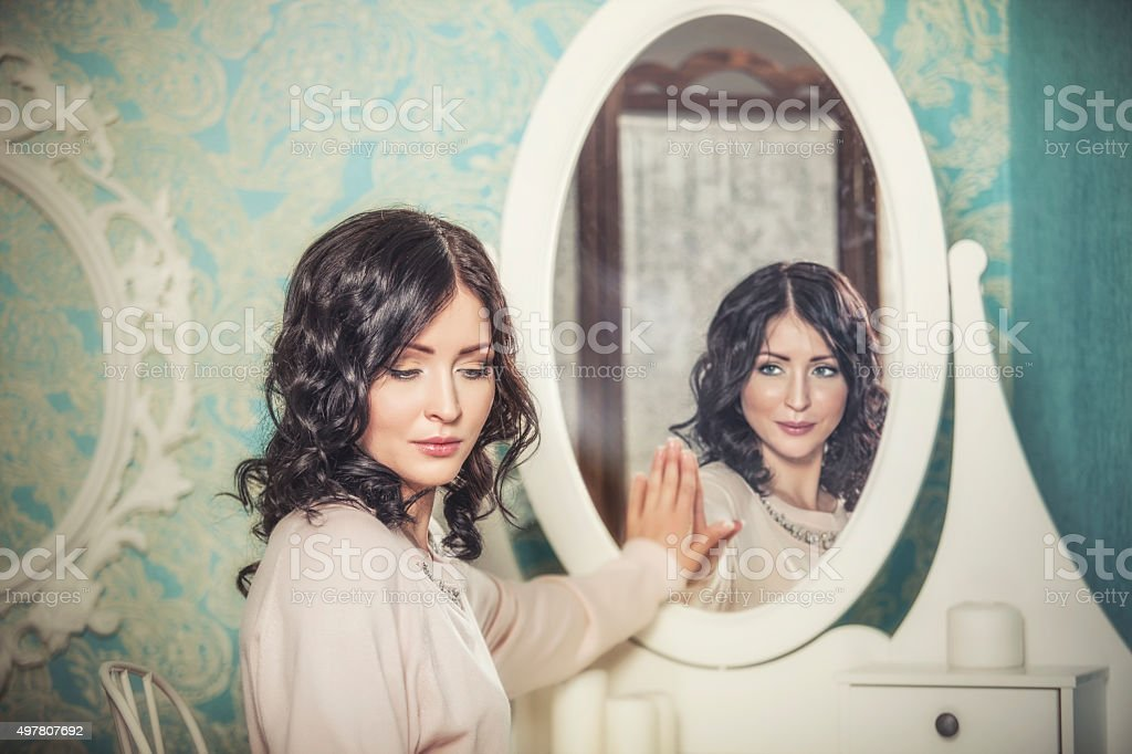 Beautiful woman in the mirror reflected the smiles magically stock photo
