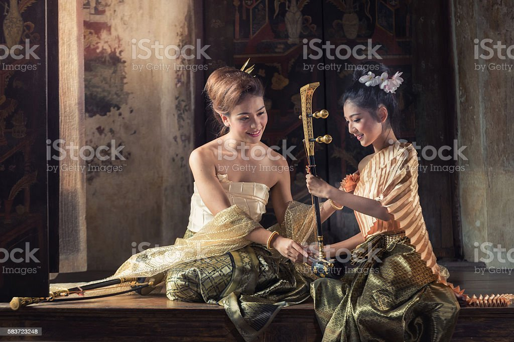 Beautiful woman in traditional dress costume playing treble fiddle. stock photo
