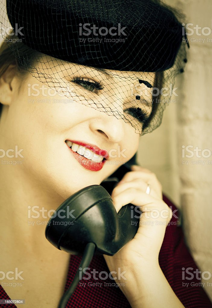 Beautiful woman in vintage forties clothing holding a telephone stock photo