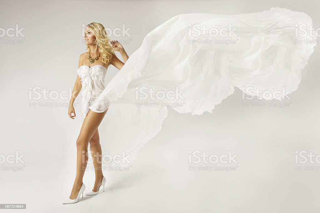 Beautiful woman in white dress with flying fabric royalty-free stock photo