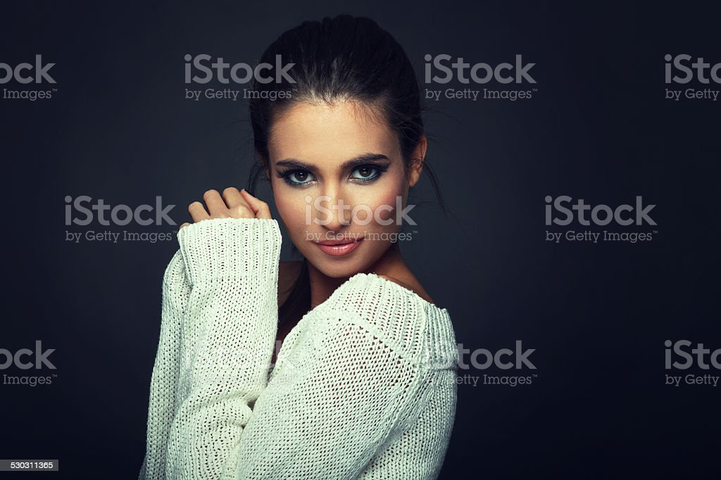 Beautiful woman in white sweater posing stock photo