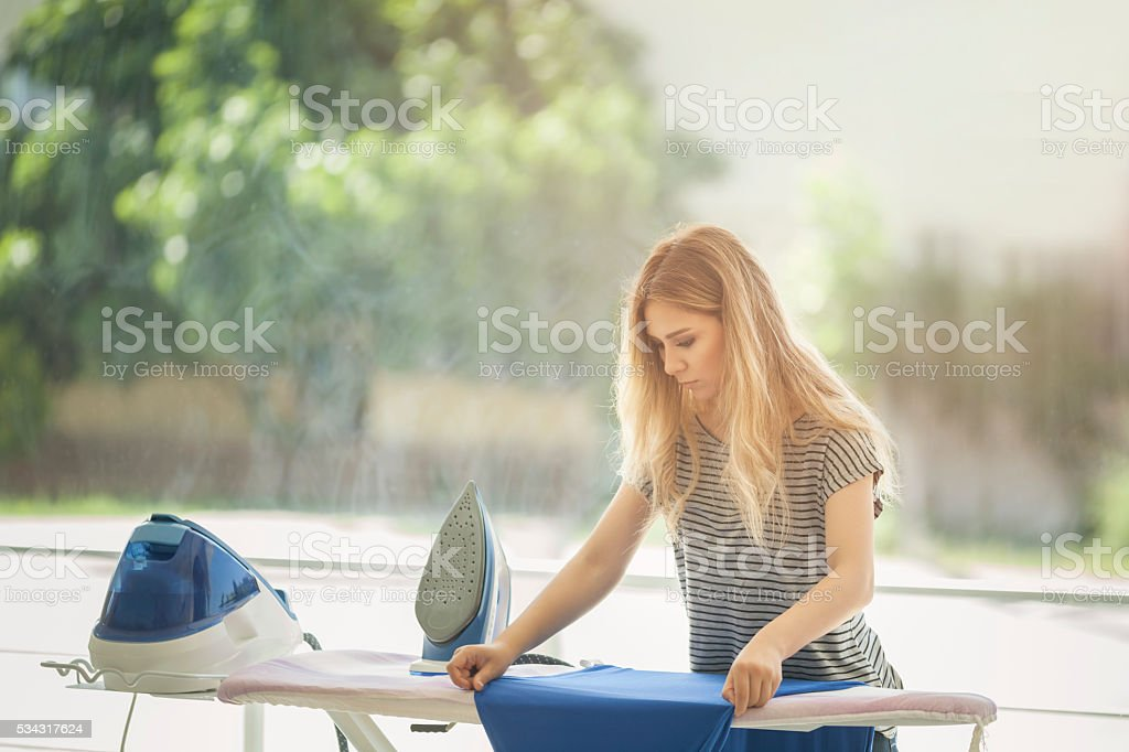 beautiful woman ironing some clothes stock photo