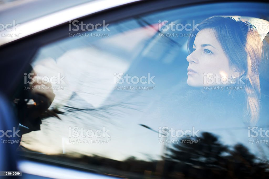 Beautiful woman is driving a car. Side view. stock photo
