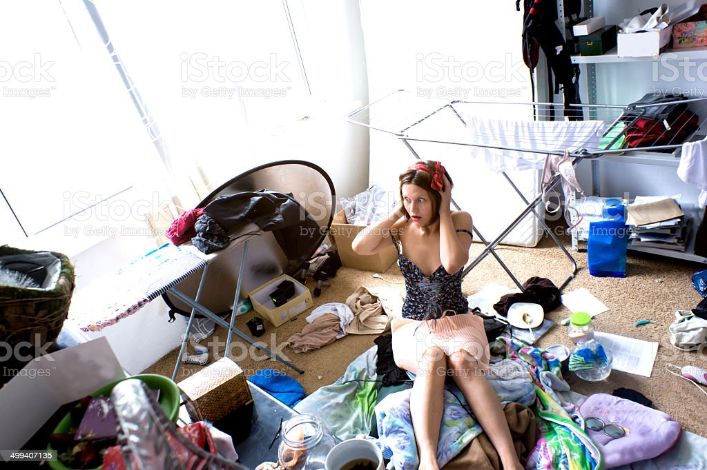 beautiful woman is expressing panic in her really messy room stock photo