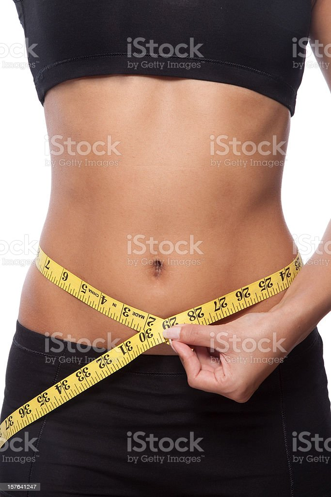 Beautiful woman is measuring her waist royalty-free stock photo