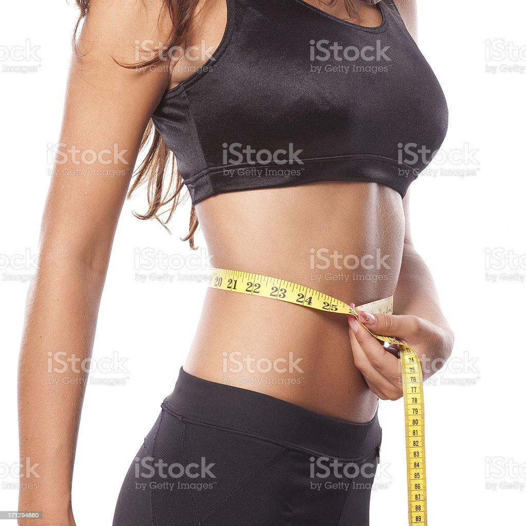 Beautiful woman is measuring her waist stock photo