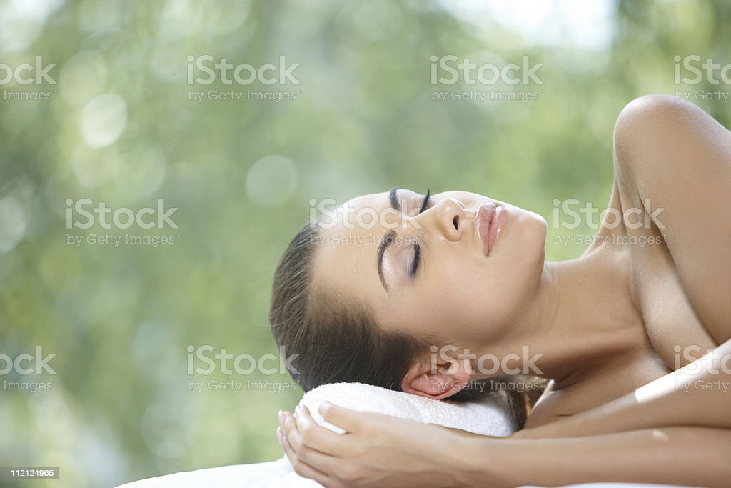 Beautiful woman is resting on spa bed stock photo