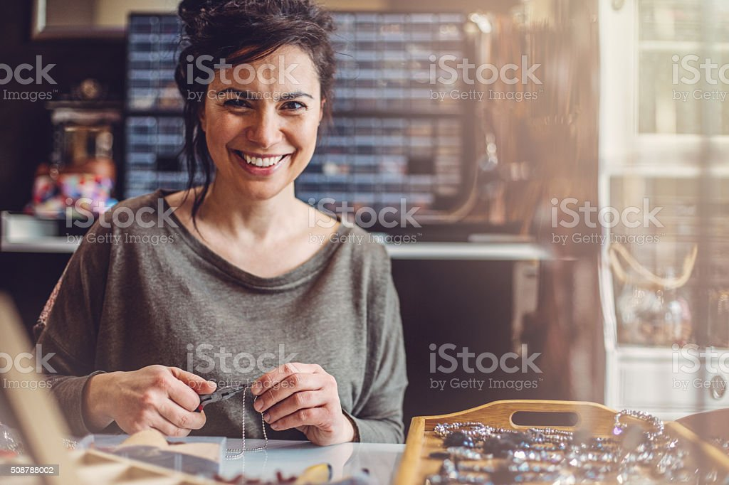 Beautiful woman jewelry maker stock photo