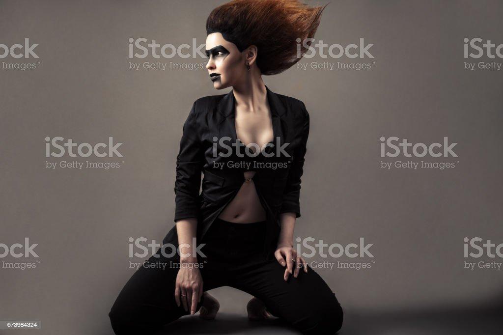 beautiful woman kneeling with lush hair and dark make-up stock photo