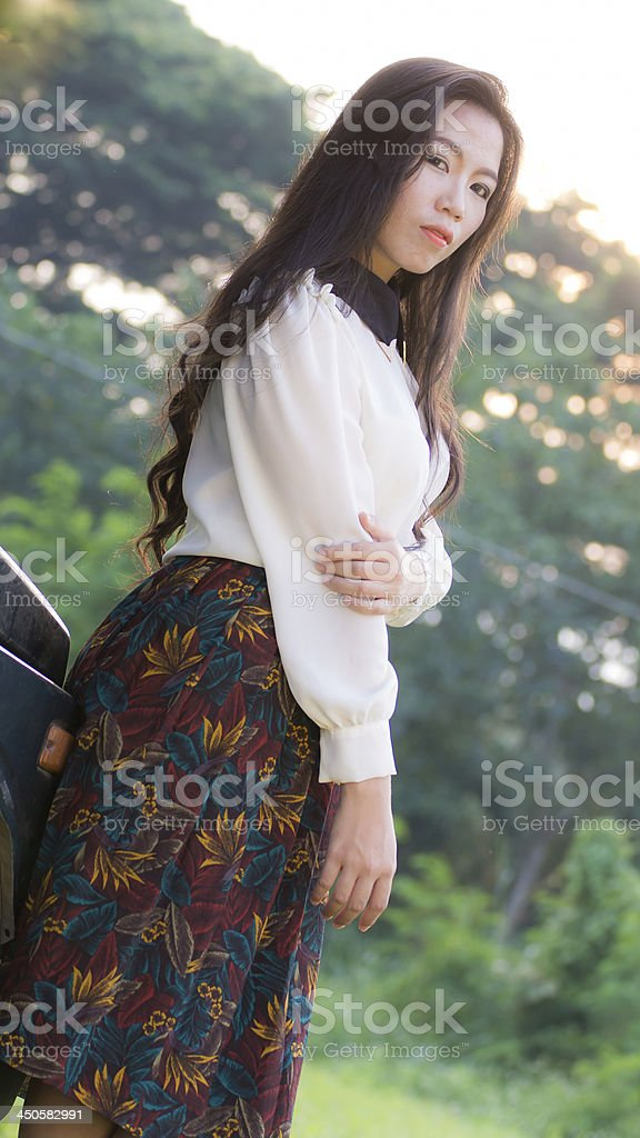 Beautiful woman leans on the car, looking at camera stock photo