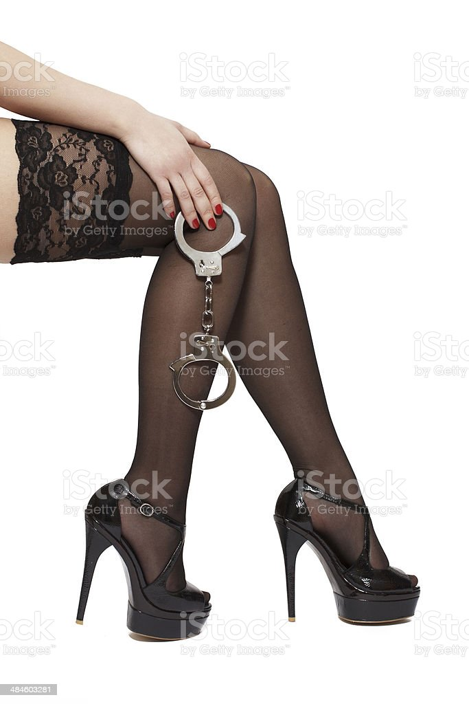 Beautiful woman legs in high heels and handcuffs royalty-free stock photo