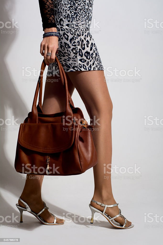 Beautiful woman legs with a brown bag stock photo