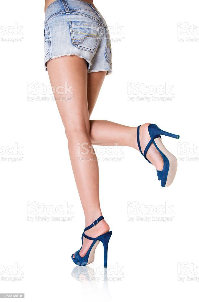 Beautiful woman legs with blue shoes and short pants. stock photo