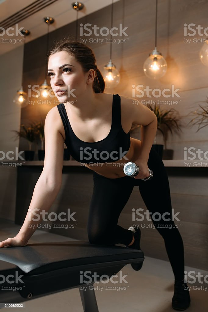 Beautiful woman lifting dumbbell at bench in gym stock photo