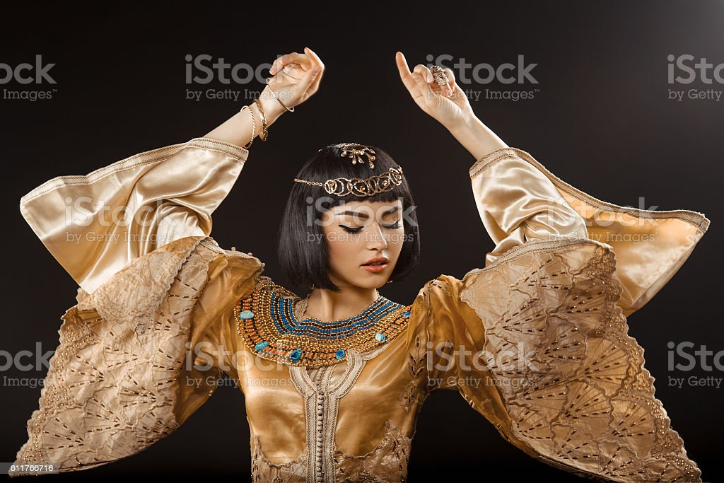 Beautiful woman like Egyptian Queen Cleopatra dancing against black background stock photo