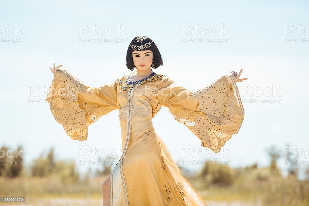Beautiful woman like Egyptian Queen Cleopatra on in desert outdoor. stock photo