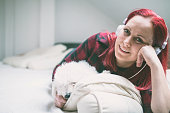 Beautiful woman listening music lying on bed at home