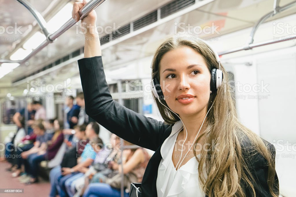 Beautiful Woman Listening Music On Her Smartphone On Subway Train stock photo