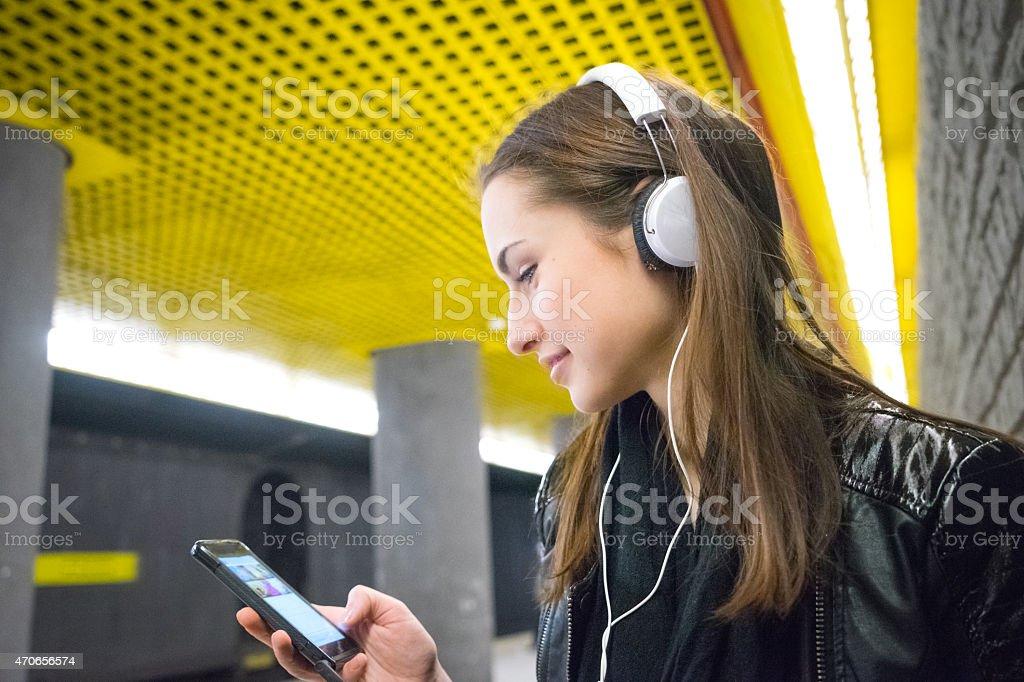 Beautiful Woman Listening Music On Her Smartphone, Subway Station stock photo