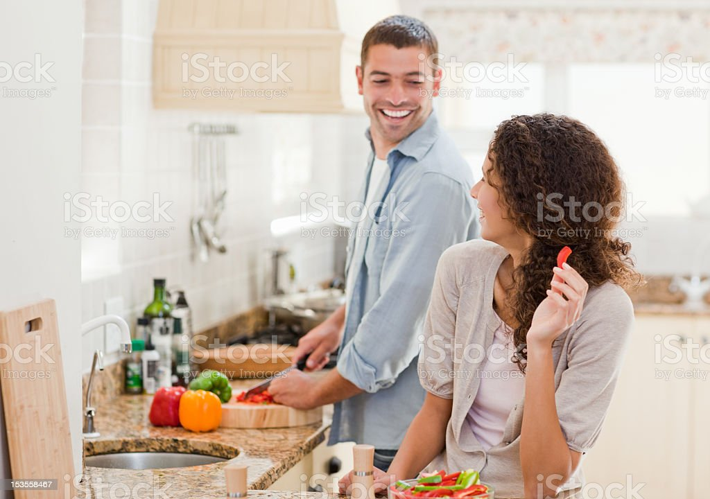 Beautiful woman looking at her husband who is cooking stock photo