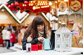 beautiful woman looking at her presents on christmas market