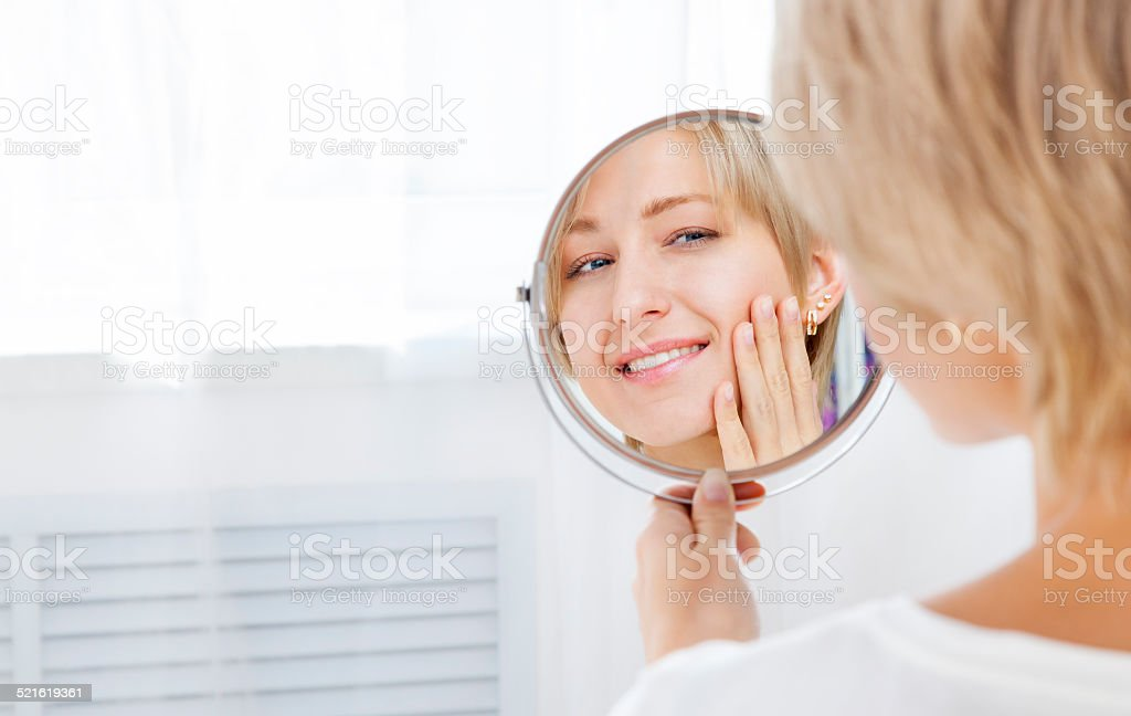 Beautiful woman looking in the mirror in the morning stock photo