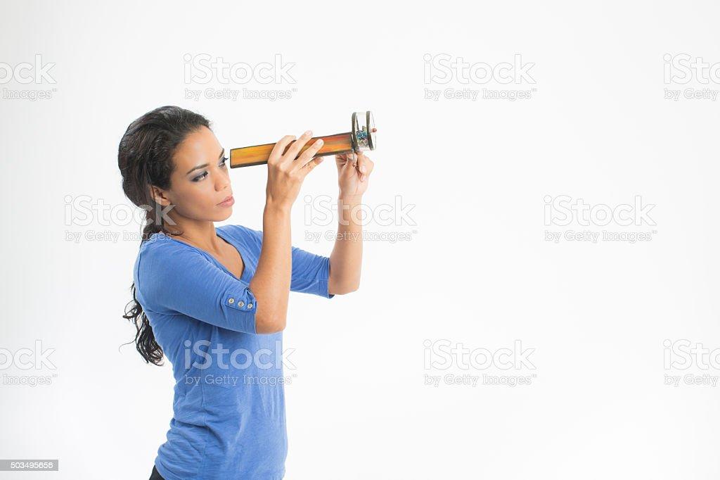 Beautiful woman looking through a  kaleidoscope. stock photo