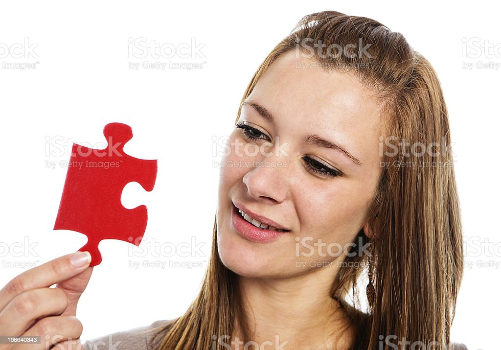 Beautiful woman looks at jigsaw puzzle piece smiling gently royalty-free stock photo