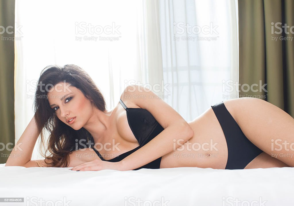 Beautiful woman lying in bed stock photo
