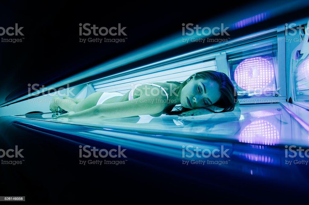Beautiful woman lying in solarium stock photo