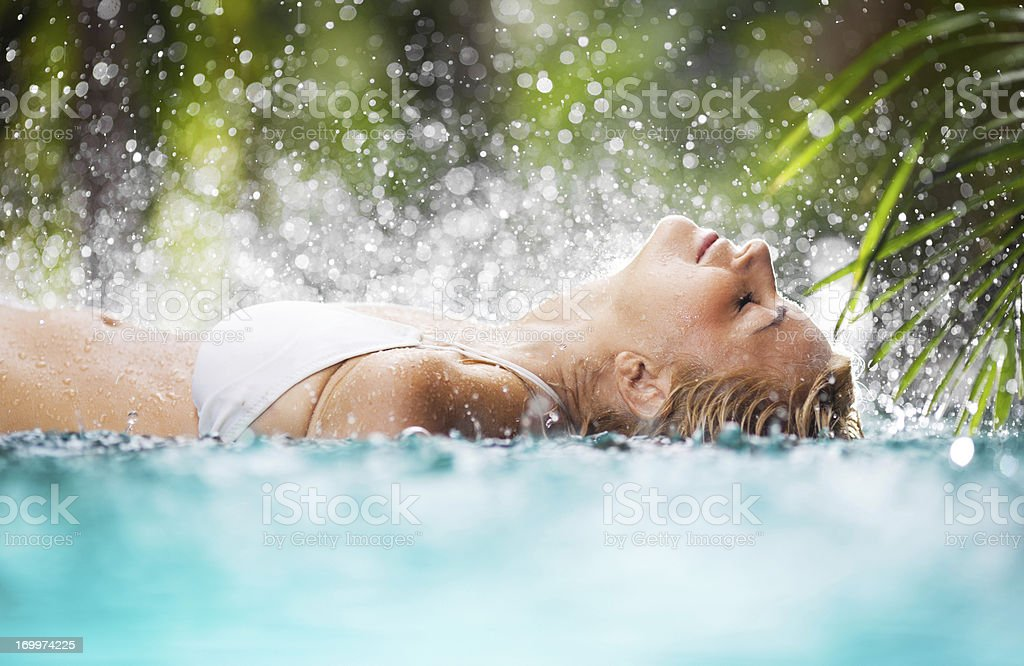 Beautiful woman lying in the tropical pool. stock photo