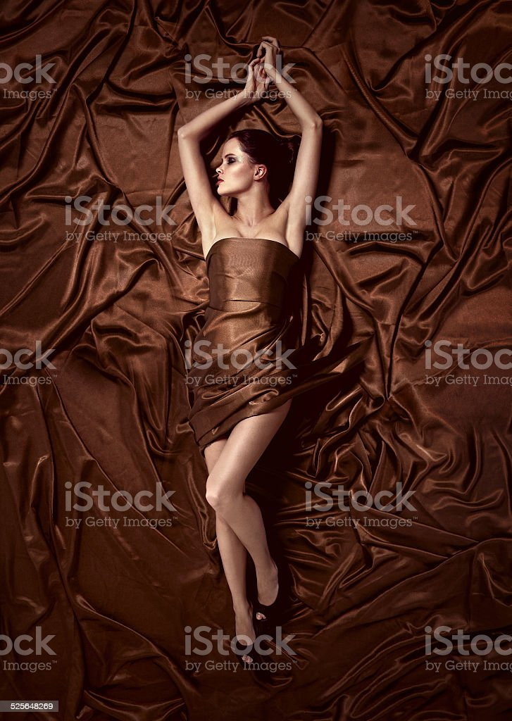 Beautiful woman lying on a chocolate fabric. stock photo