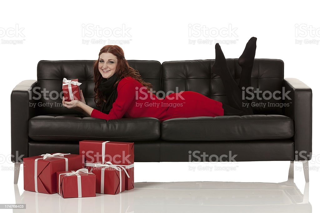 Beautiful woman lying on a couch with Christmas gifts royalty-free stock photo
