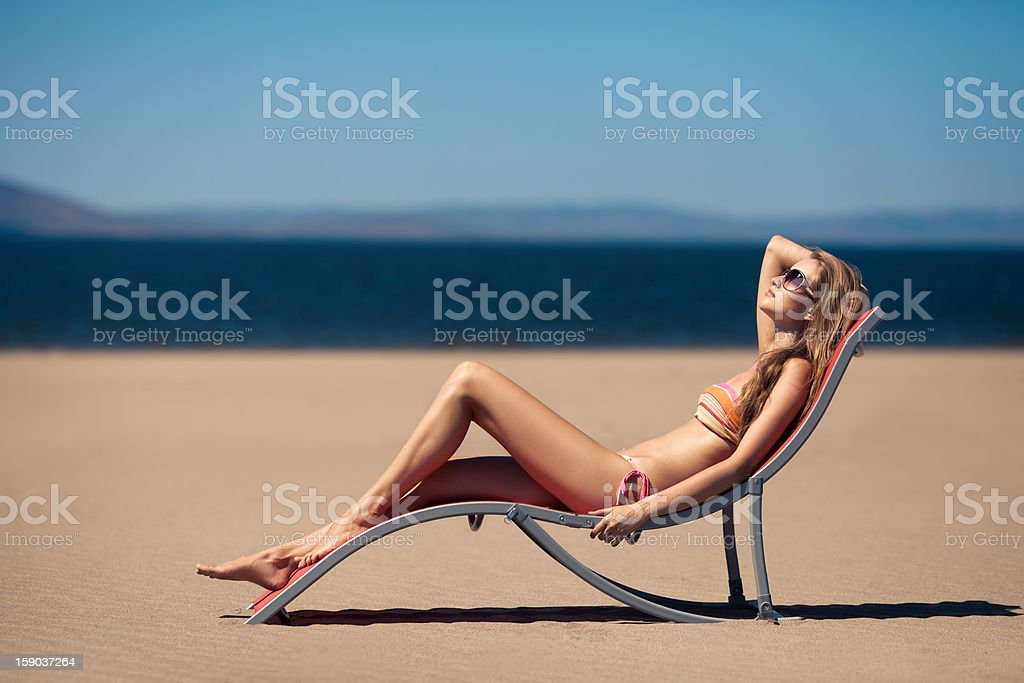 Beautiful woman lying on a deckchair at the beach royalty-free stock photo