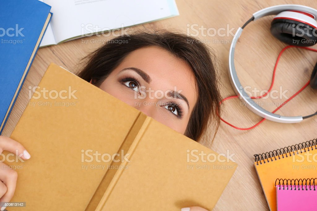 Beautiful woman lying on floor covering face with book dreaming stock photo