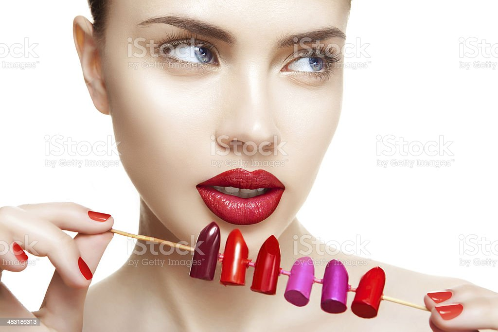 Beautiful woman makes choice between different colors of lipstick stock photo