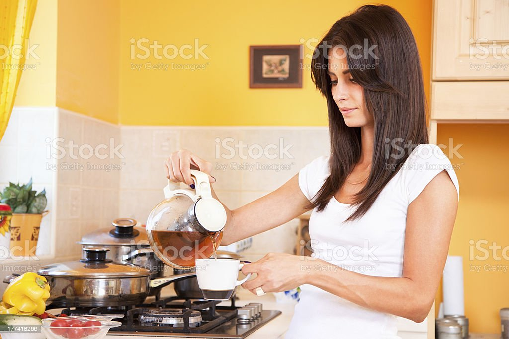 Beautiful woman making her morning tea in the kitchen stock photo