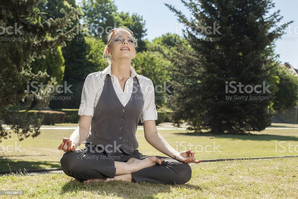 Beautiful woman meditating in the park royalty-free stock photo