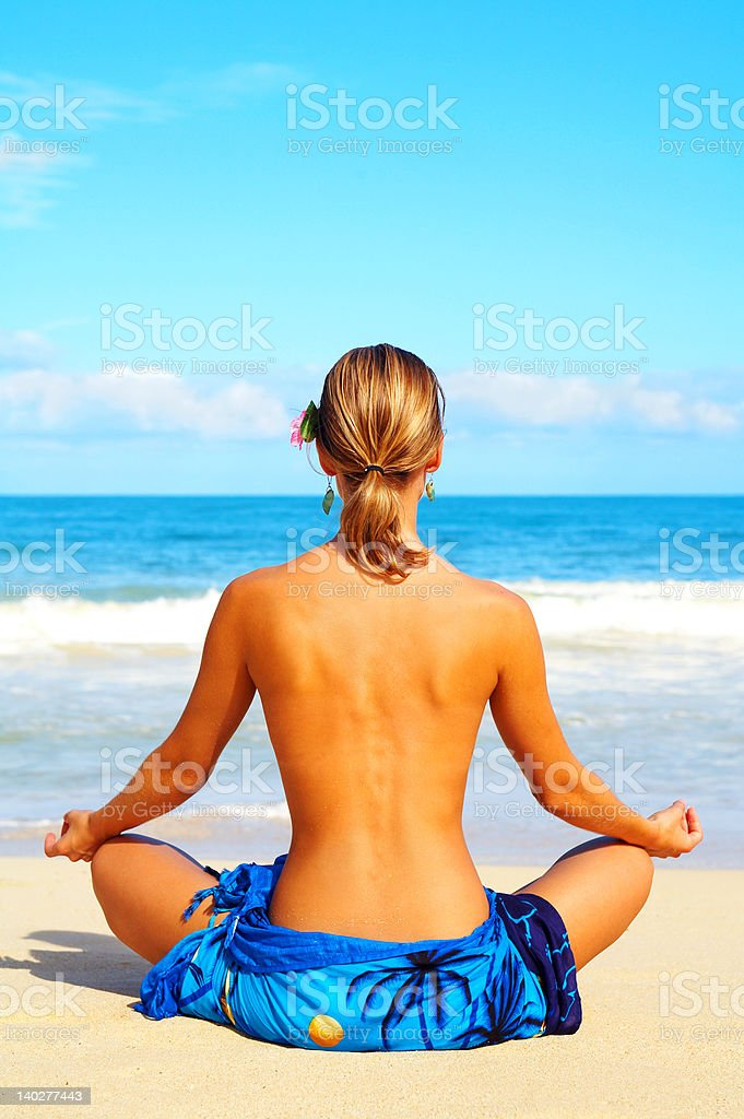 Beautiful woman meditating on the beach royalty-free stock photo