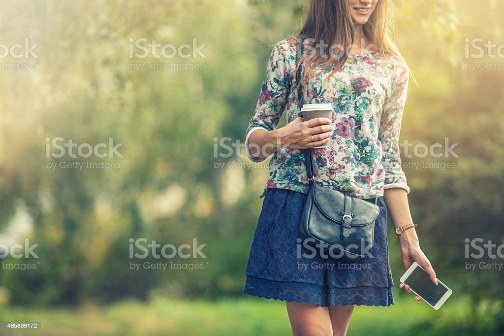 Beautiful woman model with take-away coffee and a telephone stock photo