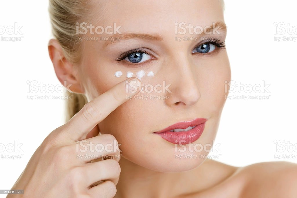 Beautiful woman moisturizing her skin stock photo